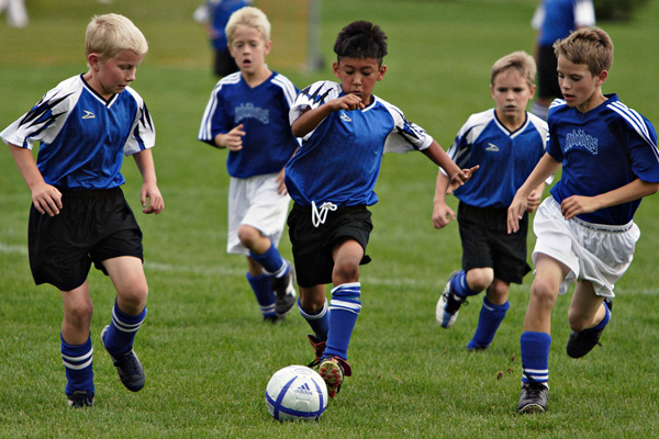 A bunch of kids playing soccer